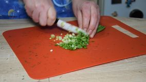 A woman is cutting a green onion.
