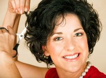 Woman cutting hair Stock Images