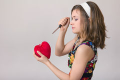 Woman cutting a heart toy with a knife. Pretty pin up woman cutting a heart toy with a kitchen knife stock photography