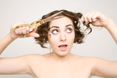 Woman cutting her curly hair Stock Photo