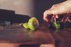 Woman cutting a kiwi Royalty Free Stock Photos