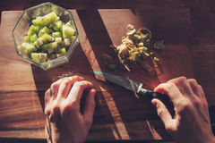 Woman cutting a kiwi Stock Photography