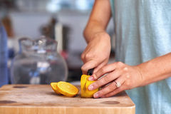 Woman cutting lemon Stock Images