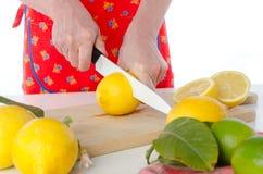 Woman cutting a lemon in half Stock Photo