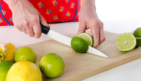 Woman cutting a lime in half Stock Photo
