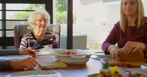Woman cutting loaf of bread on dining table at home 4k. Woman cutting loaf of bread on dining table at home. Family sitting together for breakfast 4k stock video
