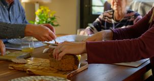 Woman cutting loaf of bread on dining table 4k. Woman cutting loaf of bread on dining table. Family sitting together for breakfast 4k stock video