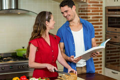 Woman cutting loaf of bread and man checking recipe book. Woman cutting loaf of bread while men checking the recipe book in kitchen at home Royalty Free Stock Image