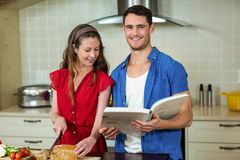 Woman cutting loaf of bread and man checking recipe book. Woman cutting loaf of bread while men checking the recipe book in kitchen at home Royalty Free Stock Images