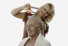 Woman cutting man's hair Stock Photography