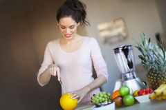 Woman Cutting Melon. Smiling woman in kitchen cutting melon. Fruit arranged for healthy eating. Food preparation. Blender for making smoothie Stock Images