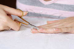 Woman cutting nails Stock Images