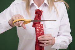 Woman cutting through a necktie with scissors Royalty Free Stock Photo