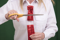 Woman cutting through a necktie with scissors Royalty Free Stock Photos