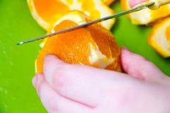 Woman cutting an orange Stock Photos