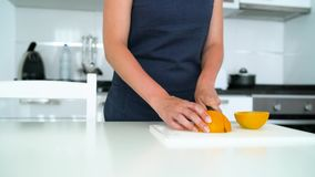 Woman cutting orange in a modern kitchen stock footage