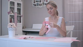 Woman cutting out butterfly from pink paper stock footage