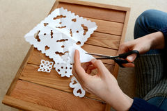Woman cutting paper into snowflake designs Stock Image
