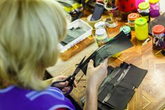 Woman cutting a part of a wallet. Blonde woman in blue unform cutting a part of a wallet with scissors. manufacturing process. jars on the background. close-up Royalty Free Stock Images
