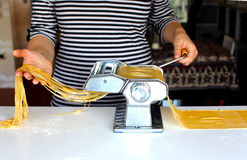 Woman cutting pasta dough on the machine at home Stock Photos