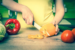 Woman cutting peppers for salad - retro style Royalty Free Stock Photography