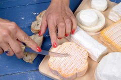 A woman cutting a piece of cheese Royalty Free Stock Images