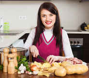 Woman cutting potatoes at table Royalty Free Stock Photography