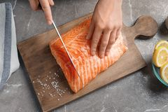 Woman cutting raw salmon fillet on wooden board. Top view Royalty Free Stock Images