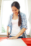 Woman cutting red fabric Stock Image