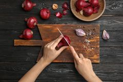 Woman cutting ripe red onion. On wooden table, top view Royalty Free Stock Image
