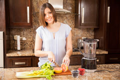Woman cutting some fruit for a juice. Gorgeous young woman cutting some fruits and vegetables to make a healthy juice using a blender Royalty Free Stock Image