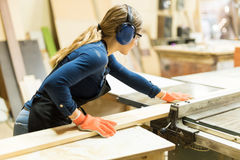 Woman cutting some wood with a table saw Royalty Free Stock Photos