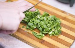 Woman cutting sorrel by knife on the wooden cooking desk. A Woman cutting sorrel by knife on the wooden cooking desk stock photo