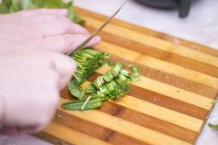 Woman cutting sorrel by knife on the wooden cooking desk. A Woman cutting sorrel by knife on the wooden cooking desk in the kitchen Royalty Free Stock Photography