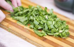 Woman cutting sorrel by knife on the wooden cooking desk. On the kitchen Stock Photos