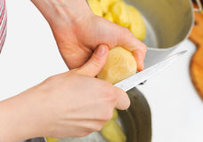 Woman cutting to peel potatoes. Kitchen working. Prepare food Stock Photos