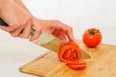 Woman cutting tomato Royalty Free Stock Image