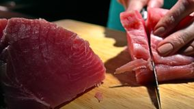 Woman cutting tuna fillet. 4K close-up dolly shot. Woman cutting tuna fillet. 4K close-up dolly video stock video