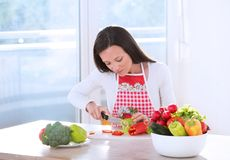 Woman cutting vegetable at table stock photos