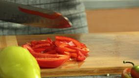 Woman cutting vegetables and cooking sweet potato quesadilla. Woman cutting onion and red pepper vegetables on wooden cutting board and cooking sweet potato stock video footage