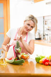Woman cutting vegetables with device at the kitchen table Stock Photography