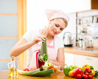 Woman cutting vegetables with device at the kitchen table. Cute woman cutting vegetables with device at the kitchen table Stock Image