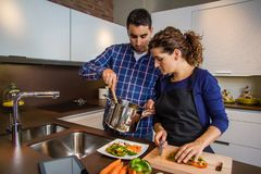 Woman cutting vegetables and man showing pot Royalty Free Stock Photo