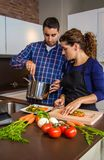 Woman cutting vegetables and man showing pot Royalty Free Stock Photos