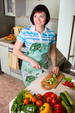 Woman cutting vegetables in the kitchen. Royalty Free Stock Photography