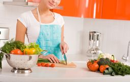 Woman cutting vegetables in kitchen interior Stock Photo