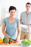 Woman cutting vegetables and man holding plates Stock Photos