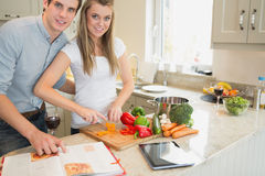 Woman cutting vegetables with man reading the cookery book Royalty Free Stock Image