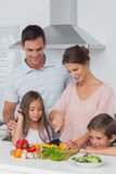 Woman cutting vegetables next to her children Stock Photos