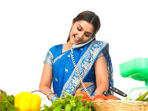 A woman cutting vegetables and talking in the phon. E at home Stock Image